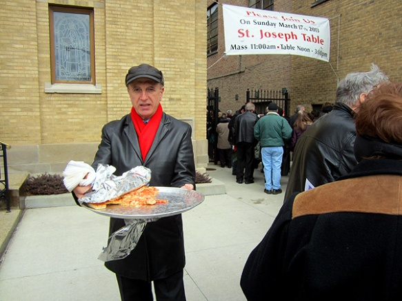 a volunteer serving pizza and wine to keep  people warm while they wait in line for St. Joseph's table, March 2013