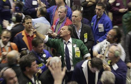 Traders in the Corn futures pit of the Chicago Board of Trade signal orders shortly after the opening bell in Chicago March 30, 2007  (Photo by Frank Polich for Reuters)